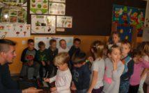 po lewej stronie zdjęcia siedzi listonosz i przedstawia sprzęt do zbierania podpisów dotykowo. dzieci stoją w kolejce, by samemu sie podpisać. w tle wielka tablica a na niej materiały dydaktyczne z przyrody.