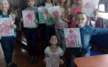 uśmiechnięte dzieci w wieku przedszkolnym przedstawiają swoje prace