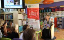 """lewy górny róg zdjęcia przedstawia plakat autorki oraz okładki jej książek.na środku zdjęcia baner z projektu""""Mali wielcy Polacy"""". pod nim niski stolik, na którym leżą książki. po prawej stronie na fotelu siedzi autorka w okularach, która w dłoniach trzyma swoje książki. lewy dół zdjęcia przedstawia 4 siedzące od tyłu sfotografowane osoby. w tle oddział dla dzieci"""