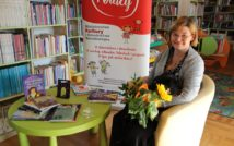 po lewej stronie zdjęcia niski stolik,a na nim książki napisane przez autorkę. na środku zdjęcia fragment baneru z projektu. po prawej stronie siedząca pisarka trzymająca bukiet kwiatów, a na jej kolanach leżący pies. w tle oddział dla dzieci.