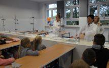 zdjęcie przedstawia klasę chemii w Liceum Ogólnokształcącym im. Mikołaja Kopernika. doł zdjęcia przedstawia siedzące tyłem dzieci. w centralnej górnej części zdjęcia stoi uczennica wraz z nauczycielką chemi i przedstawia eksperyment z balonem
