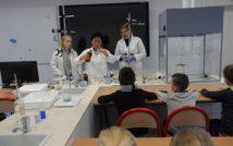 zdjęcie przedstawia klasę chemii w Liceum Ogólnokształcącym im. Mikołaja Kopernika. doł zdjęcia przedstawia siedzące tyłem dzieci. w centralnej górnej części zdjęcia stoją 2 uczennice wraz z nauczycielką chemii i wykonują eksperyment wykorzystując ciecz z butelki i probówkę