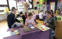 dzieci siedzą na kanapie i podłodze tworząc plastyczne prace