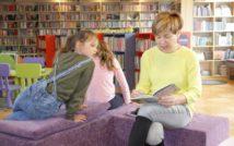 kobieta siedzi i czyta ksiązkę, wokoł niej dwie dziewczynki