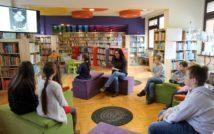 siedząca kobieta czyta ksiązkę, wokół niej siedzą dzieci.w tle oddział