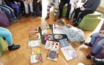 dziewczynka siedzi na podłodze i pisze na kartce,wokół niej książki