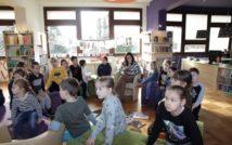 siedząca kobieta czyta ksiązkę, wokół niej siedzą dzieci