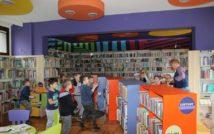 bawiące i biegające dzieci wśród półek Oddziału dla Dzieci i Młodzieży