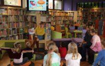 dzieci siedzą na kanapie. kobieta siedzi na fotelu i trzyma książkę.w tle oddział