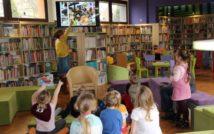 dzieci siedzą na kanapie. kobieta wskazuje na ekran.w tle oddział