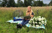 siedząca kobieta na kocu w trzyma książkę. koło niej ptaszek w klatce. za nią łąka