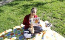 siedząca kobieta na dywanie w okularach trzyma książkę. w tle trawa