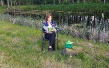 kobieta siedzi na krześle i czyta z otwartej książki, koło niej na pniu siedzi żaba ogrodowa.za nią staw