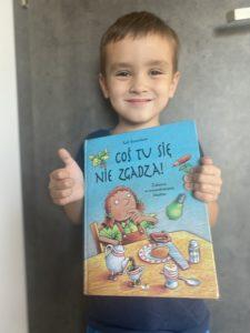 """uśmiechnięty chłopiec trzyma książkę """"Coś tu się nie zgadza"""""""