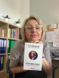 kobieta trzymająca książkę Kena Robinsona Kreatywne szkoły. W tle regał z ksiażkami