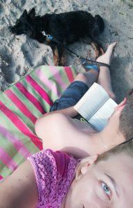 na pierwszym planie fragment twarzy kobiety, która opiera się o plecy czytającego mężczyzny. u góry zdjęcia w oddali leżący pies