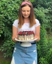 Młoda kobieta w plenerze, trzymająca w rękach tort.