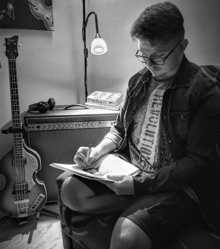 Młody mężczyzna w okularach siedzący w fotelu. W ręku trzyma kartki i ołówek. Z tyłu gitara i wzmacniacz. Na nim słuchawki, dwie książki. Za nim lampa. U góry fragment obrazu.
