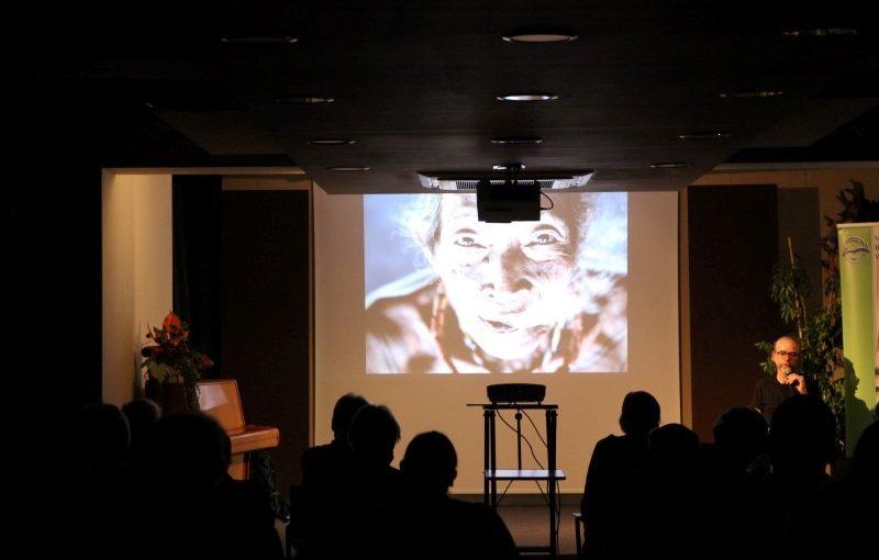 Ekran i projektor. Na ekranie twarz mężczyzny. W lewym rogu pianino, na nim kwiat. W prawym rogu mężczyzna z mikrofonem. Ludzie siedzący tyłem.