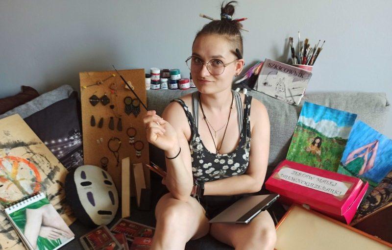 Młoda kobieta w okularach siedząca na tapczanie. W ręku trzyma pędzel, na lewym kolanie notatnik. Za kobietą obrazki, farby, pędzle i szkicownik.