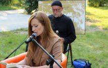 Siedząca w fotelu kobieta, przed nią mikrofon. Z tyłusiedzi mężczyzna, za nim plansza.