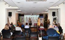 16 osób na sali. 13 osób siedzi, trzy osoby stoją. Dwie z nich stoją na scenie. Z tyłu ekran. Po lewej stronie pianino, na nim bukiet. Za pianinem baner. Po prawej stronie, w głębi baner z napisem: bibliolook. Po bokach antyramy z obrazami. Na nimi głośniki.