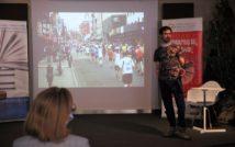 młody mężczyzna w t-shircie na tle zdjęcia z maratonu