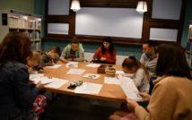 Osiem osób siedzących przy stole. Trzy osoby piszą. Na stole kartki i koszyczki. Osoba po prawej stronie trzyma kartkę. Z tyłu po lewej stronie regały z książkami. Za osobami okno. U góry dwie lampy.