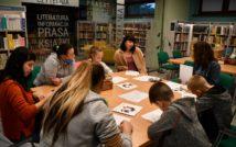 Osiem osób siedzących przy stole. Dwie osoby piszą. na stole kartki i foldery. Za osobami regały z książkami. Po lewej stronie napis: czytelnia, literatura, informacja, prasa, książki. Obok, po prawej stronie napis: prasa, literatura, książki.
