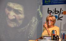 Siedząca kobieta z wzniesionym palcem do góry. Przed nią stolik, na stoliku książki i matrioszka z wizerunkiem mężczyzny. Z tyłu na ekranie starsza kobieta. Z tyłu po prawej stronie baner z napisem: bibliolook.
