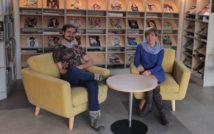 siedzący męzczyzna i kobieta na fotelach.za nimi regały z prasą