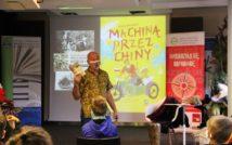 mężczyzna w koszuli z krótkim rękawem trzymający książkę. za nim na zdjęciu plakat ilustracyjny pary w motorze Machiną przez Chiny. w tle na zdjęciu