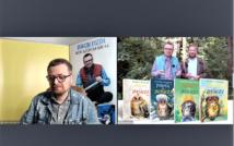 screen przedstawia uśmiechniętego mężczyznę w okularach w koszuli w kratę i kurtce dżinsowe.po prawejstronie dwóch mężczyzn, przed nimi 4 okładki książek