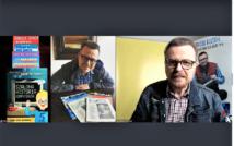 Prawa strona screenu przedstawia siedzącego mężczyznę, przed nim na stole jego publikacje. po lewej stronie mężczyzna w okularach, w koszuli w kratę ni kurtce dżinsowej