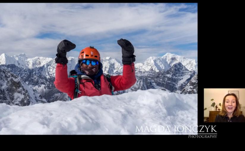 Mężczyzna w kasku i okularach z podniesionymi do góry rękoma. Przed nim śnieg. Za nim ośnieżone góry. U góry niebo i chmury. W prawym dolnym rogu kobieta, która mówi. Niżej napis: Magda Jończyk. Poniżej napis: Photography.