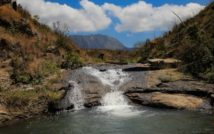 Wodospad i rzeka. Po bokaxh wzgórza. Z tyłu góra, u góry niebo i chmury.