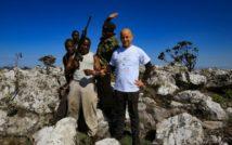 Pięciu mężczyzn stojących pośród skał. Jeden mężczyzna trzyma w rękach strzelbę. Z tyłu krzaki i niebo.