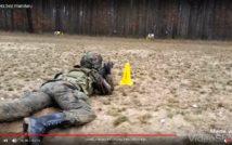 screen przedstawia zdjęcie osoby leżącej w stroju bojowym trzymającej strzelbę. w tle las