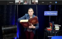 * w centralnej części zdjęcia znajduje się Piotr Szumny, trzyma wielką otwartą księgę , po prawej stronie widnieje stół, a na nim książki, w prawym górnym rogu zdjęcie tablicy z napisem ul. Piotr Szumny
