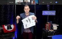 * w centralnej części zdjęcia znajduje się Piotr Szumny, trzyma gazetę, by stworzyć sztuczkę, po prawej stronie widnieje stół a na nim książki, w prawym górnym rogu zdjęcie tablicy z napisem ul. Piotr Szumny