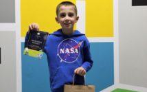 uśmiechnięty chłopiec w swojej prawej ręce trzyma dyplom.w lewej torbę z nagrodami. w tle kolorowa ściana.