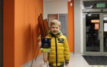 chłopiec w kurtce w prawej ręce trzyma dyplom.w lewej torbę z nagrodami. w tle hol biblioteki.