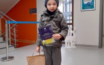usmiechnięty chłopiec w czapce i kurtce w swojej lewej ręce trzyma dyplom.w prawej torbę z nagrodami. w tle hol biblioteki.