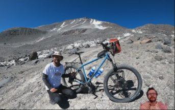 Mężczyzna z rowerem na tle wulkanu, który był celem wyprawy