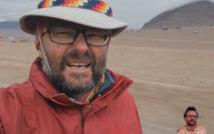 portret podróżnika w kapeludszu na tle pustyni i wulkanu, który jest celem jego wyprawy