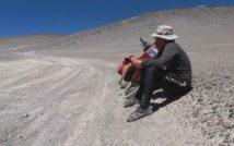 piaszczysta pustynna droga zakręcająca w lewą stronę, po prawej na pierwszym planie siedzi odpoczywający rowerzysta, za nim widoczny rower
