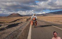 asfaltowa droga przez pustynię, w tle pasmo gór. centralnie mężczyzna jadący na obłożonym bagażem rowerze
