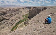 kanion pustynny, na jego prawym brzegu siedzący mężczyzna