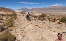 kamienista droga pod górę, po której mężczyzna jedzie rowerem