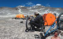 panorama pustynna, w tle pasmo górskie, na drugim planie namioty i obozowisko, na pierwszym planie mężczyzna naprawiający koło od roweru